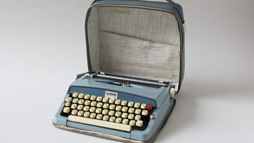 A blue typewriter in an opened blue leather case