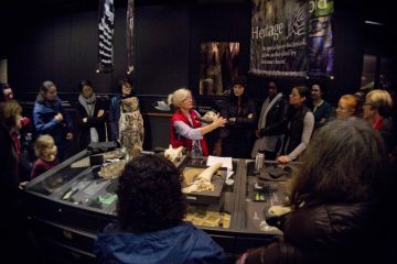 Sheila, a museum interpreter in a red vest, stands around a bank of drawers in the tetrapod collection delivering a museum tour, she is holding a cougar skull and is pointing to the teeth. On the surface in front of her are two wings, a taxidermied owl, and two skulls. A small group of museum visitors of varying ages, genders, and ethnicities stand and listen.